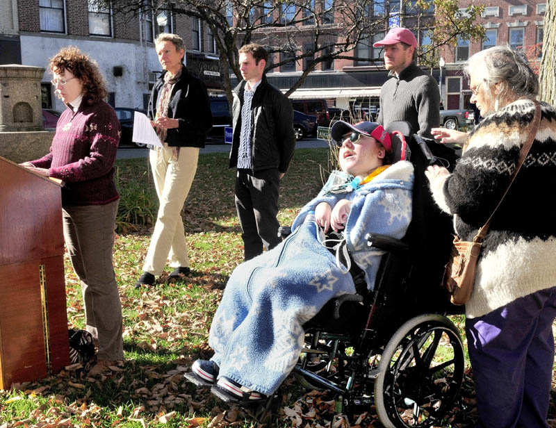 Deborah Klane of Fairfield speaks about the impact of rising health care costs for small business owners, as health care provider Ellie Symonevich attends to Klane's disabled son, Evan, during a rally in Waterville on Wednesday. Behind Klane is Waterville Mayor Karen Heck, Jonathon Hillier and Erik Thomas.
