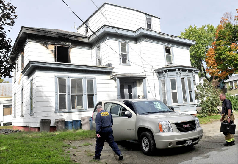 INVESTIGATION: Ken MacMaster, left, of the state Fire Marshal's Office, and Waterville firefighter John Gromek prepare to enter an apartment building in Watervile on Wednesday to determine the cause of a fire that damaged the building on Tuesday.