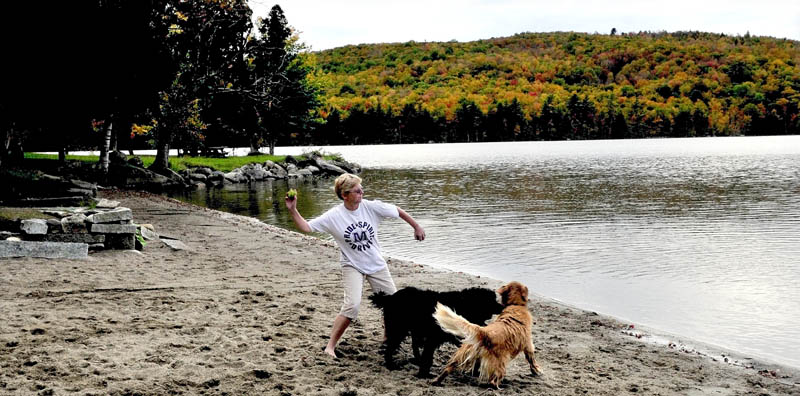 Staff photo by David Leaming Lori White of Skowhegan throws balls for her dogs at the beach and picnic area at Lake George Regional Park East in Canaan.