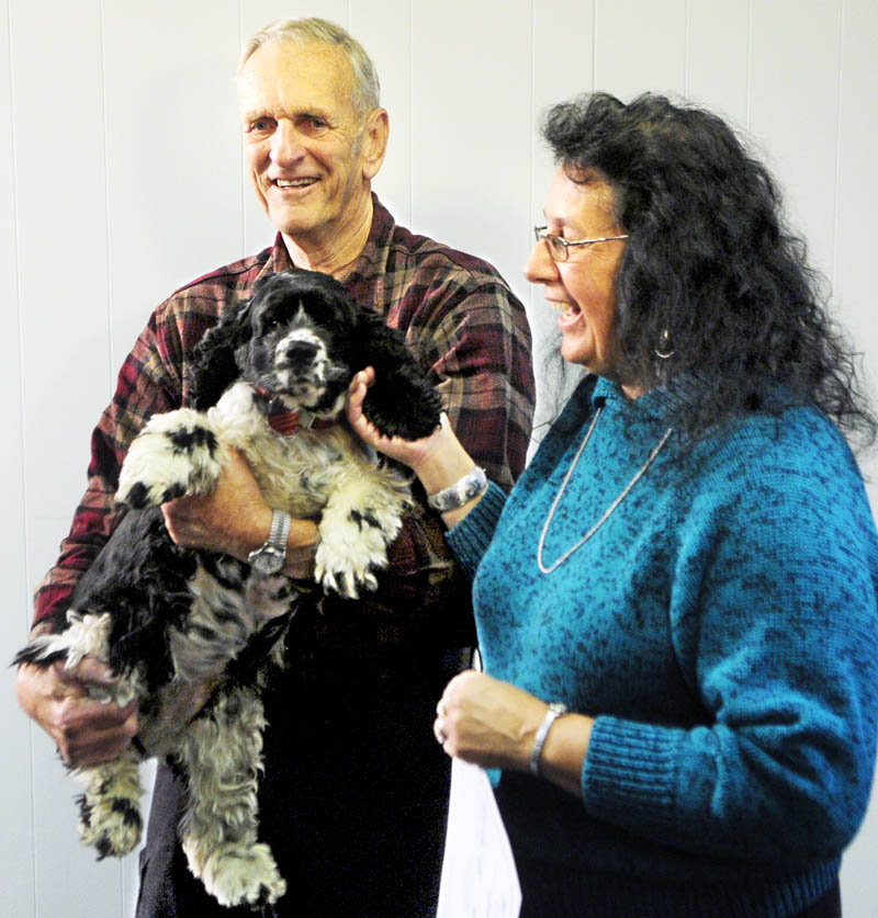 Lottery winner Linda Von Oesen, of Fairfield, right, and her husband Bob Von Oesen speak to reporters as they pet Abby, their three-year-old cocker spaniel during a news conference on this morning in Hallowell.