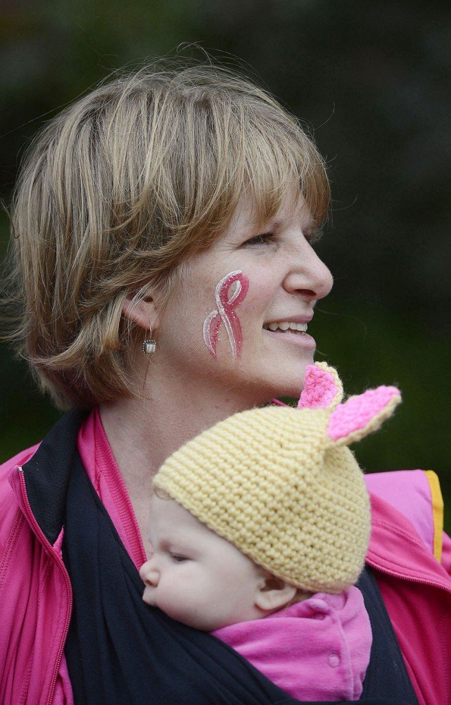 Cristin Doughty of Saco, with a pink ribbon painted on her face, holds her daughter Ava, 3 months, before the start of the Making Strides walk Sunday in Portland.