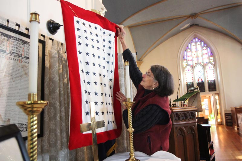 Dorothy Washburne sets up a side altar to replicate one used during World War II, at Christ Church in Gardiner on Friday. The Episcopal church, located on Dresden Avenue, will be having a special service to honor veterans on Sunday, beginning at 10 a.m. Washburne said the church still has one member of the original World War II honor roll, far left.