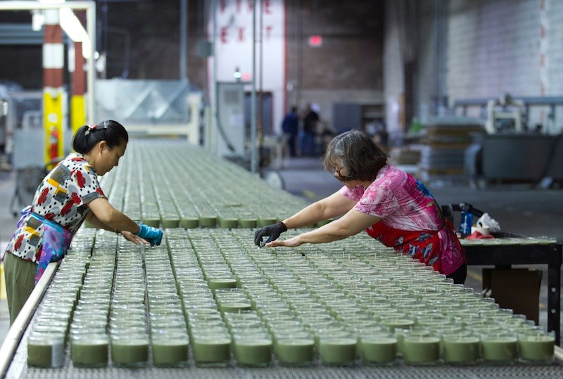 In this Aug. 30, 2012 file photo, production line workers, Xiao Yins-Wong, left, and Chui M. Wong, straighten the wick in the candles at Chesapeake Bay Candle factory in Glen Burnie Md. The U.S. economy grew at a 2.7 percent annual rate from July through September, much faster than first thought. The strength is expected to fade in the final months of the year because of uncertainty about looming tax increases and government spending cuts. (AP Photo/Jose Luis Magana, File)