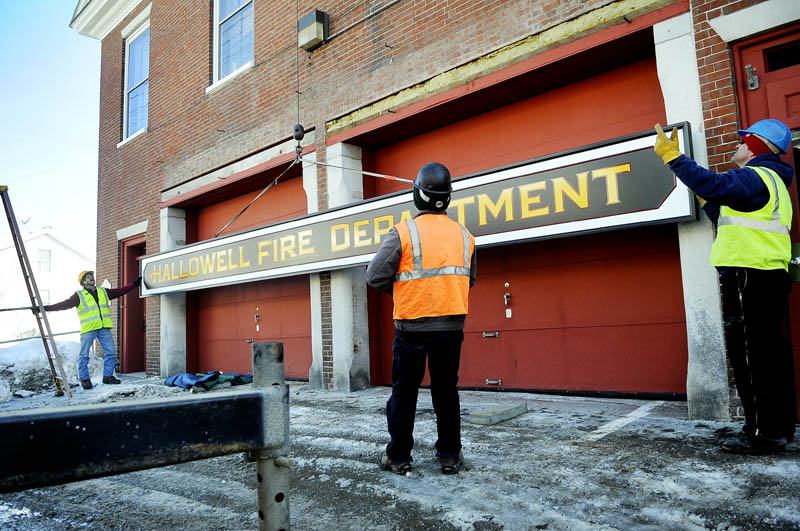 Workers hang a sign on the exterior of the Hallowell Fire Department station on Second Street in February 2011.