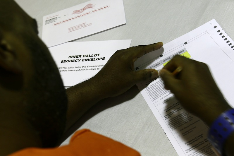 In this photo taken Oct. 24, 2012 , a prisoner votes at the D.C. Jail in Washington. The voters at this southeast Washington polling place were all dressed alike: orange jumpsuit, white shoes. And when they finished voting they went back to their cell block, not back to work. Still, voting inside the D.C. Jail looked a lot like voting at precincts around the country.(AP Photo/Jacquelyn Martin)