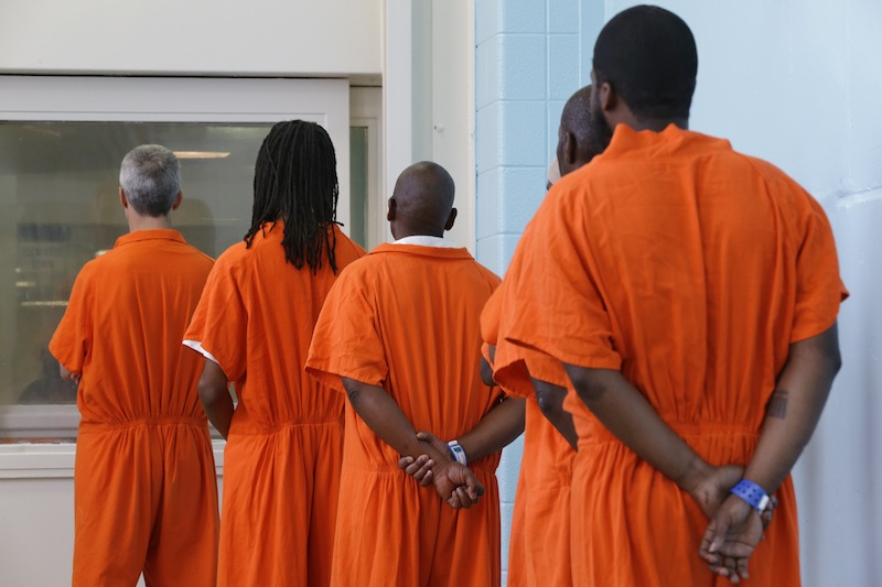 In this photo taken Oct. 24, 2012, prisoners line up to vote at the D.C. Jail in Washington. The voters at this southeast Washington polling place were all dressed alike: orange jumpsuit, white shoes. And when they finished voting they went back to their cell block, not back to work. Still, voting inside the D.C. Jail looked a lot like voting at precincts around the country. (AP Photo/Jacquelyn Martin)