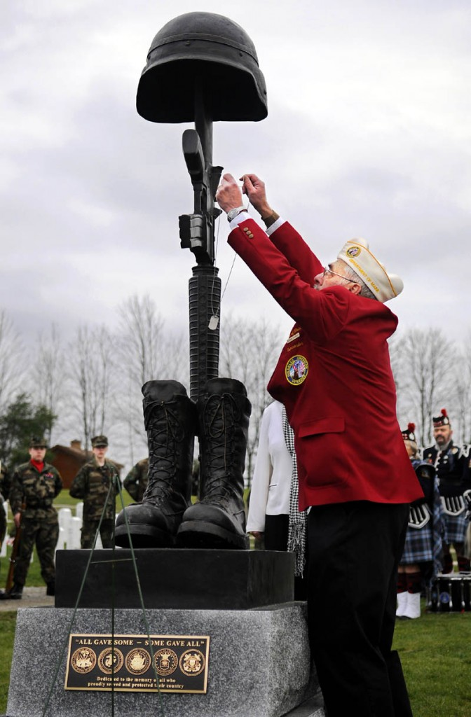 Disabled veteran Richard Fournier hangs dog tags Sunday on the new Battlefield Cross Memorial Monumentn during a dedication ceremony at the Maine Veterans' Memorial Cemetery in Augusta.