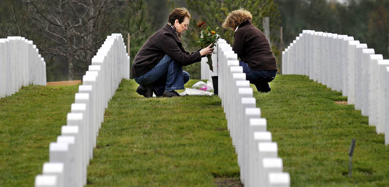 Lisa Crowell, left, lays flowers Sunday on the headstone of her husband, Wayne, with her sister-in-law, Sheila Crowell, at the Maine Veterans' Memorial Cemetery in Augusta. Wayne C. Crowell, of Wayne, who died in May, received two Purple Hearts while serving with the Army in Vietnam.