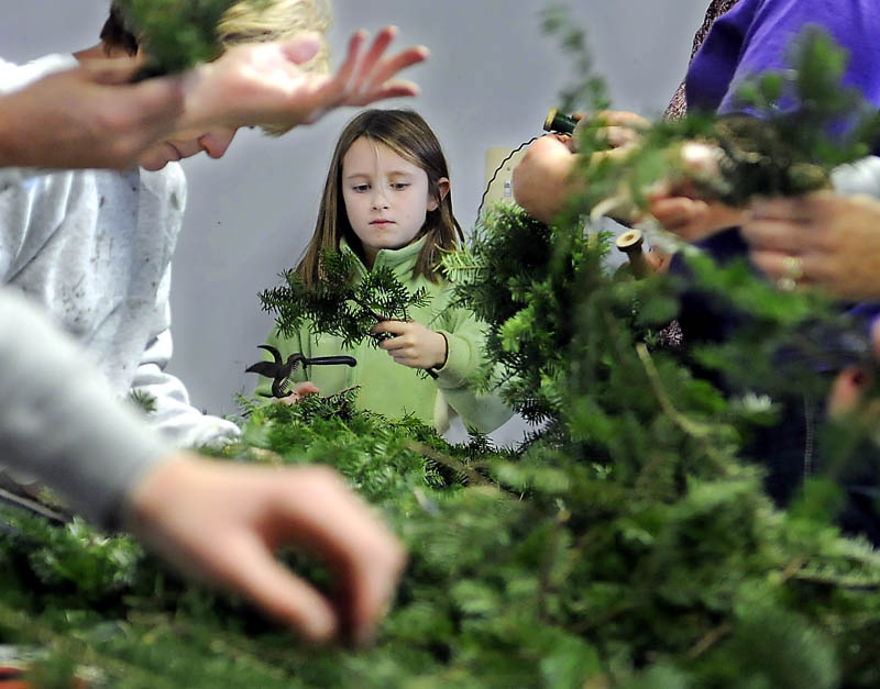 Many hands wrap and clip boughs Sunday at the Windsor Historical Society, during the annual wreath-making event. Andrea Richardson, 8, of Windsor, is one of several who volunteered to make the holiday decorations to adorn the houses and barns at the Society.
