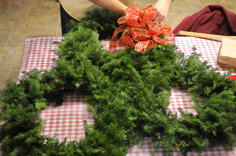 Priscilla Brann wraps bows around wreathes created at the Windsor Historical Society on Sunday.