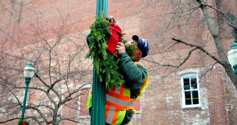 Gardiner Buildings and Grounds Supervisor Pat Chadwick hangs a wreath Wednesday on Water Street. Gardiner crews were preparing the downtown for the annual Christmas tree lighting, scheduled for Saturday at 6 p.m.