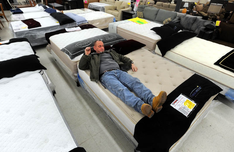 Chester Hanscom, of Fairfield, tests a mattress while shopping at Mardens Surplus and Salvage on Kennedy Memorial Drive in Waterville on Black Friday.