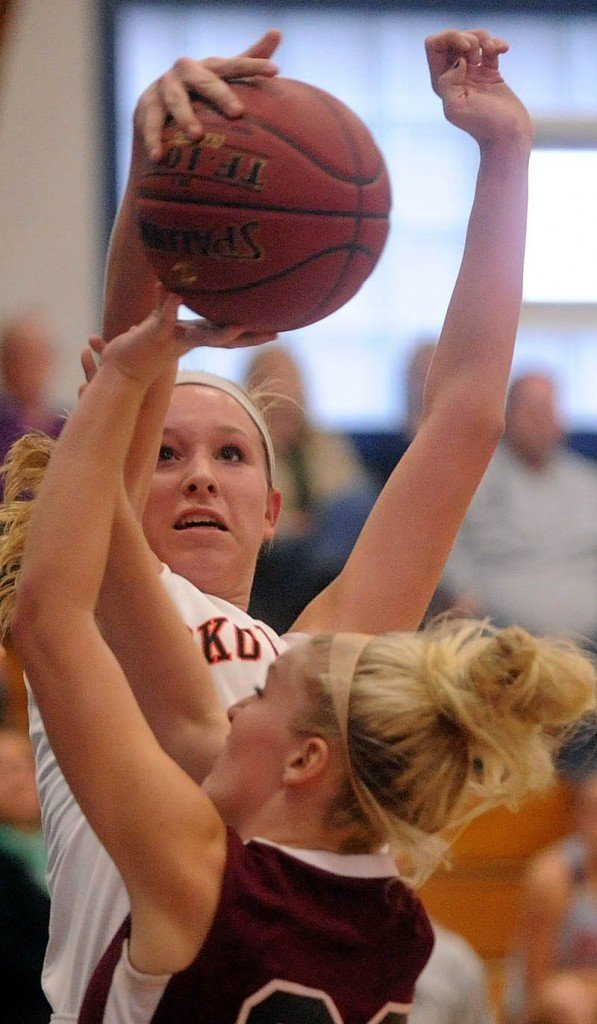 Staff photo by Michael G. Seamans Skowhegan High School's Morgan Buker, 32, rejects a shot by Nokomis High School's Lindsay Whitney, 22, in the first half of girls basketball action in the Bulldog Classic at Lawrence High School in Fairfield Saturday.