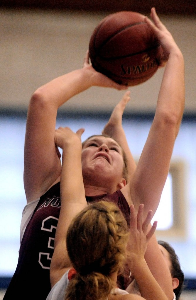 Staff photo by Michael G. Seamans Nokomis High School's Anna Mckenzie, 30, shoots over a Skowhegan High School defender in the second half of girls basketball action in the Bulldog Classic at Lawrence High School in Fairfield Saturday.