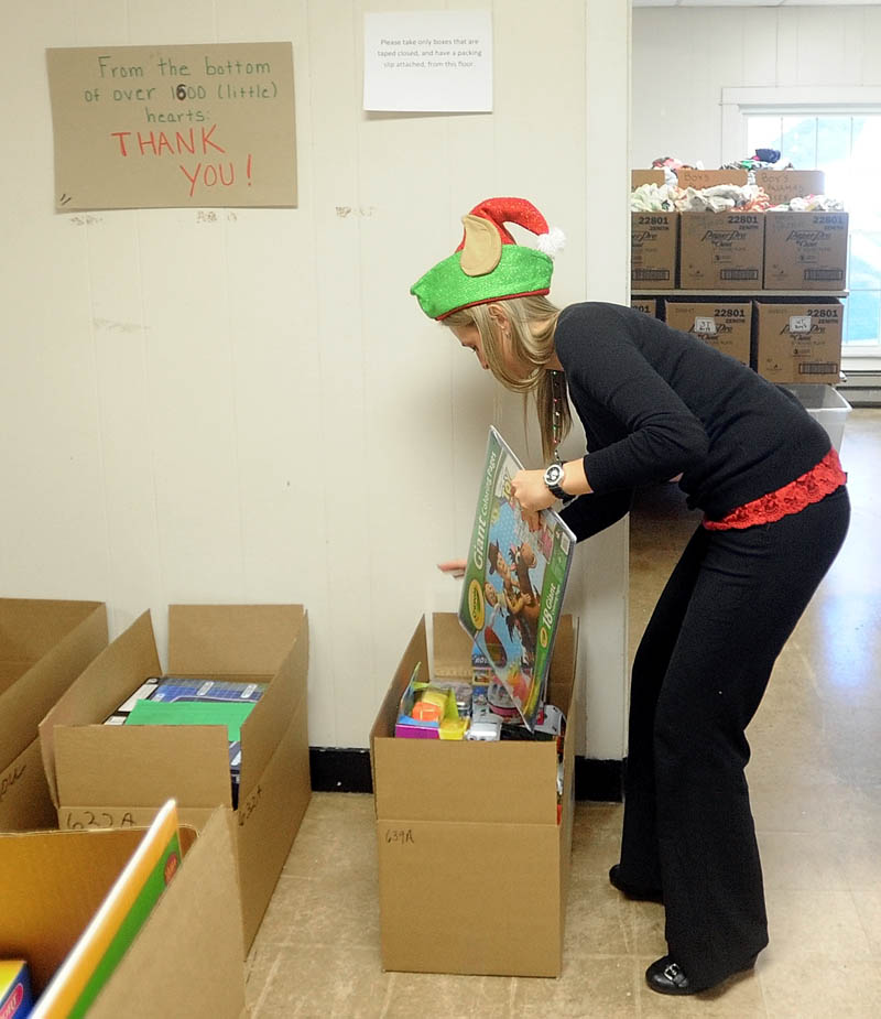 Kasie Flowers, of the Waterville Housing Authority, packs gift boxes to be distributed to disadvantaged children in the area for the holidays, at the Maine Children's Home for Little Wanderers in Waterville, on Thursday.