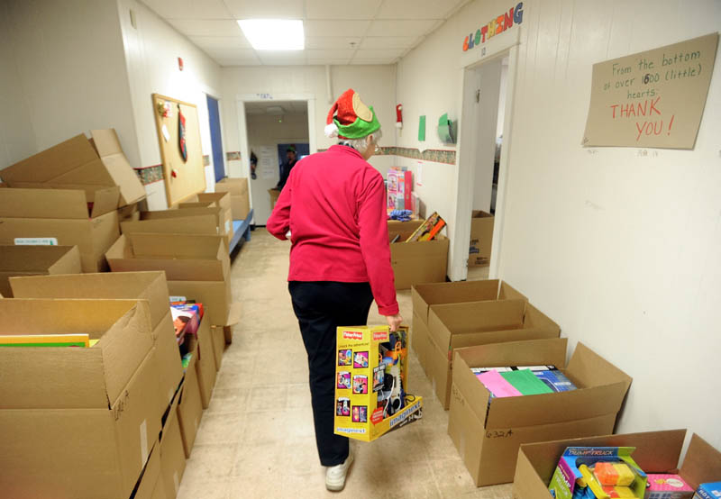 Peggy Walker, of the Waterville Housing Authority, packs gift boxes to be distributed to disadvantaged children in the area for the holidays, at the Maine Children's Home for Little Wanderers in Waterville, on Thursday.