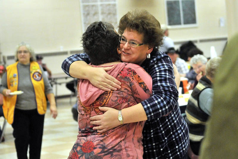 Jill Dart, right facing, hugs volunteer Shelli Mellows, after her meal at the 23rd annual community Thanksgiving Day dinner at Messalonskee High School in Oakland, on Thursday. Dart's husband recently died, and she attended the community dinner to surround herself with friendly smiles and a hot meal for the holiday.
