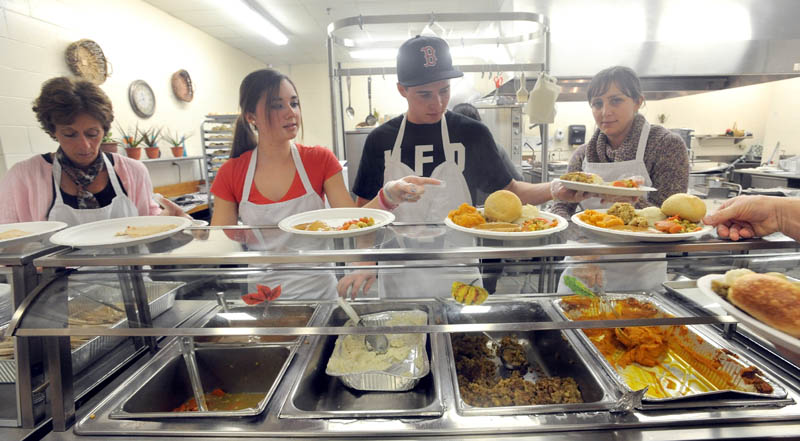 Volunteers, from left to right, Donna Russon, Alyssa Smith, 16, Ethan Foss, 18, and Sarah Harding, 30, serve up turkey and all the fixings at the 23rd annual community Thanksgiving Day dinner at Messalonskee High School in Oakland, on Thursday.