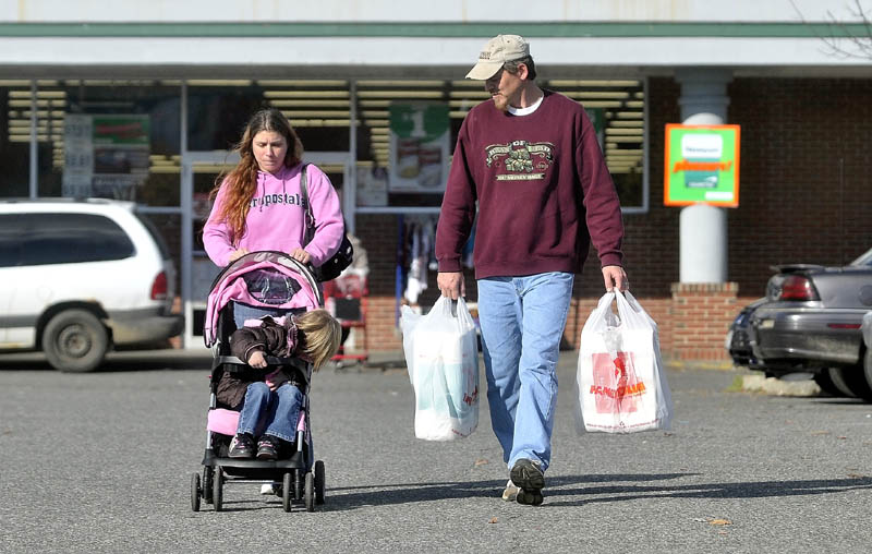 Janet White pushes her daughter, Savannah LaBrie, in a stroller as Jeff White carries groceries, after shopping at Family Dollar in Waterville on Nov. 2. Their car was also destroyed in the same fire that burnt their Waterville home, leaving the family to rely on friends and family to get around town. On this day they couldn't find a ride and had to walk the two miles from home to the store.