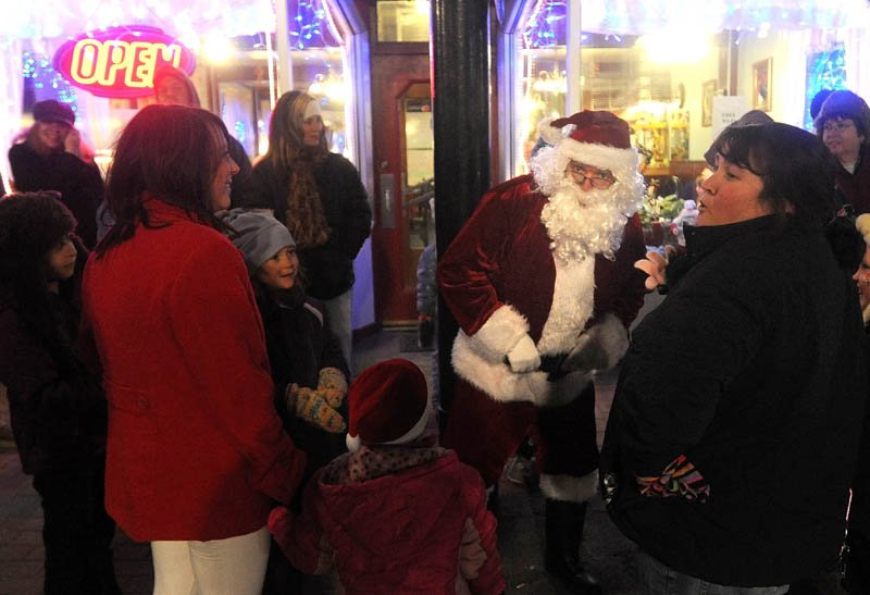 Santa Claus talks with parade-goers at the Holiday Stroll parade, on Water Street in downtown Skowhegan, on Friday.