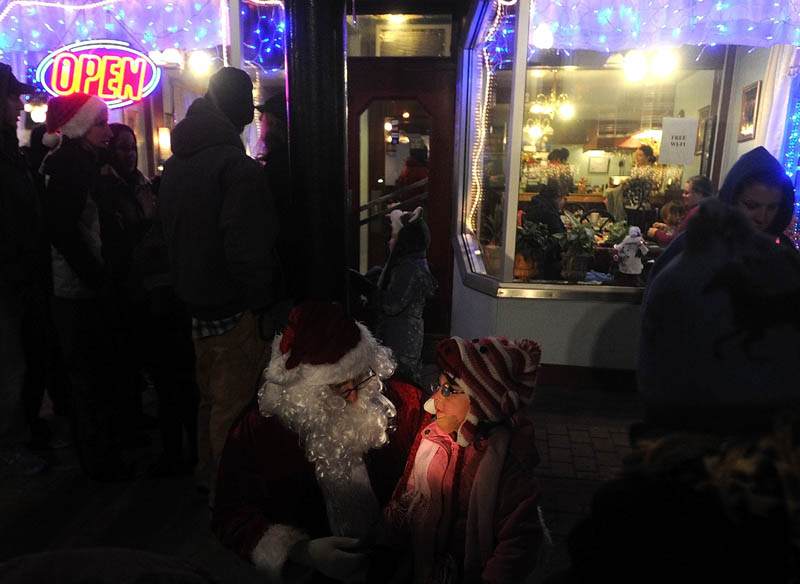 Santa Claus listens carefully to Laura Harding, 3, of Harmony, as she offers a list of gifts she would would like to see under her Christmas tree this year, at the Holiday Stroll parade, on Water Street in downtown Skowhegan, on Friday.