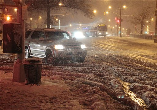 Cars navigate Queens Boulevard during a snow storm on Wednesday in the Queens borough of New York.