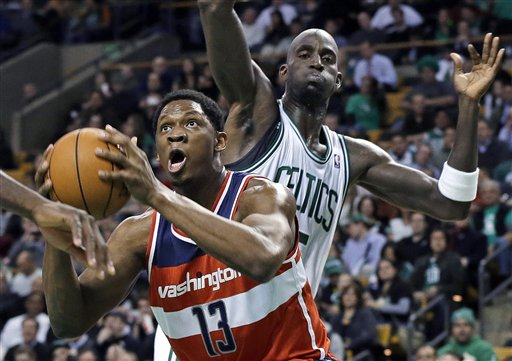 Washington Wizards forward Kevin Seraphin (13) drives to the basket past Boston Celtics forward Kevin Garnett during the first half of an NBA basketball game in Boston on Wednesday, Nov. 7, 2012. (AP Photo/Elise Amendola) TD Garden