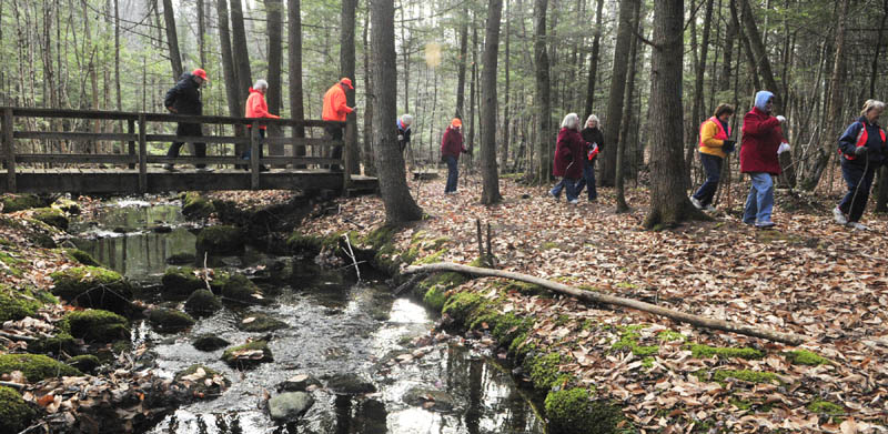 Hikers cross a bridge on Friday morning at the Fogg Conservation Area in Readfield.