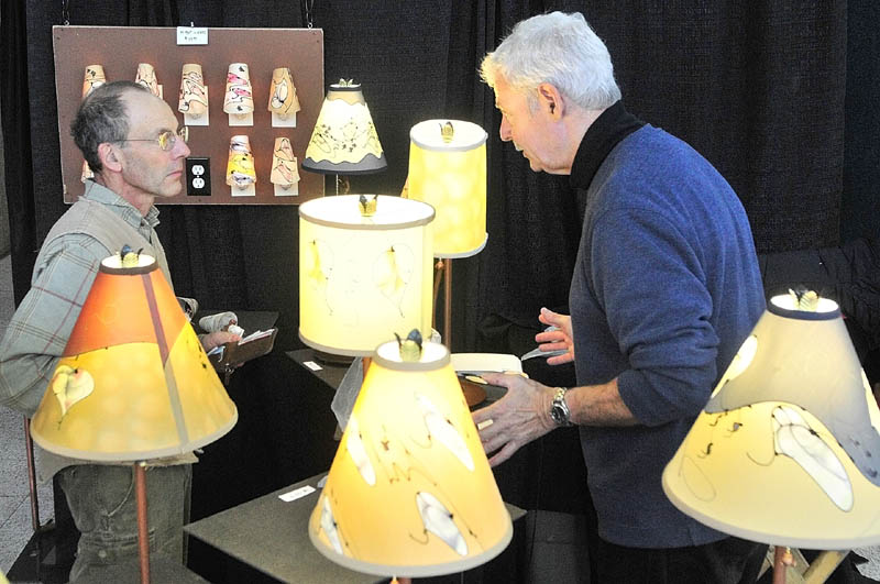 Customer Kyrill Schabert, of Jefferson, left, chats artist Stuart Loten about his lamps and shades on Saturday afternoon during 16th Annual Crafts at the Museum Show in Augusta. The Maine State Museum is located off of State Street just south of the State House and show continues today from 10 a.m.to 4 p.m.