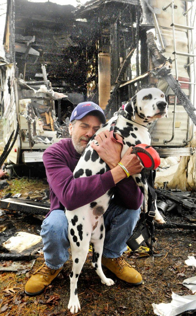 Robert Wing kneels with his Dalmatian, Brie, held tightly in front of their charred motor home on Tuesday afternoon in Augusta.