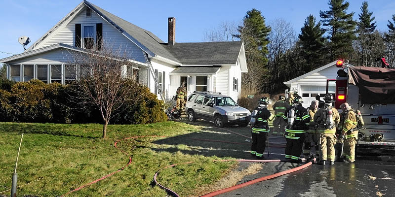 Firefighters work at 283 Spring Road after extinguishing a fire there this afternoon.