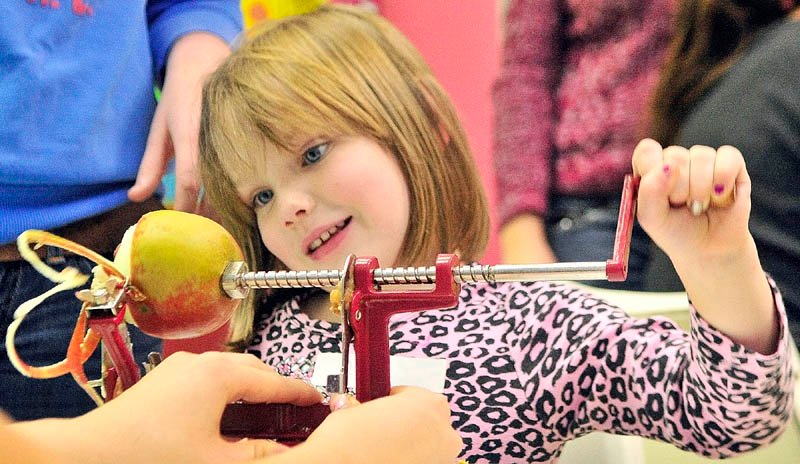Lauren Miller, 5 of Winthrop, cranks an apple peeler-slicer on Wednesday afternoon at the Children's Discovery Museum in Augusta. She and other children made a crust, prepared apples and covered it all with a crumb topping during the museum's annual Make, Take and Bake event.