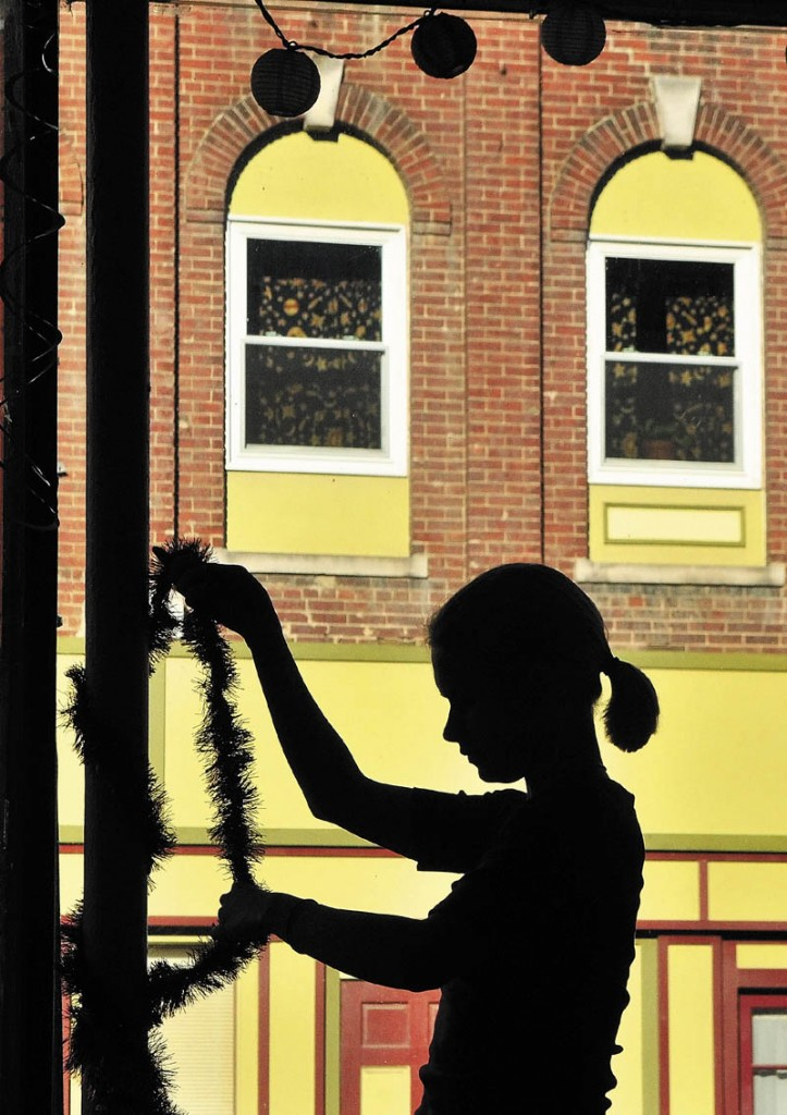 Raeanna Gormatov wraps colorful tinsel around a pole on Tuesday afternoon inside the front window of Lisa's Legit Burritos on Water Street in downtown Gardiner.