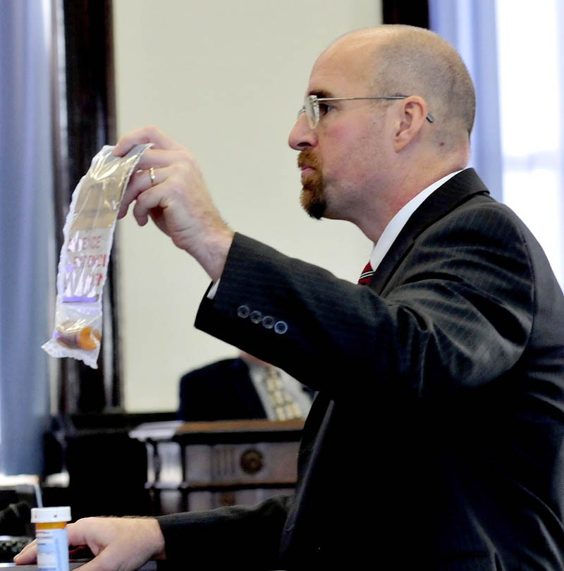 Assistant Attorney General Don Macomber holds a bag filled with prescription drugs in his opening statement against defendant Robert Nelson, on trial in the death of Everett Cameron in Somerset County Superior Court on Monday.