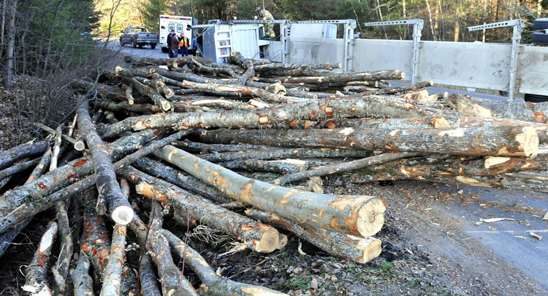Skowhegan firefighters inspect the cab of an overturned truck that rolled over near Sappi Fine Papers, on U.S. Route 201 in Skowhegan, on Monday, and spilled a load of logs.
