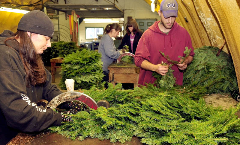 Central Maine Wreath Co. workers are busy making holiday wreaths, garlands, canes, crosses and hearts at the Skowhegan business on Thursday. Owner Tom McCarthy said he expects to make 20,000 wreaths this season. From left are Kristie Meader, Retta Giguere, Ida Beane and Gary Meader.