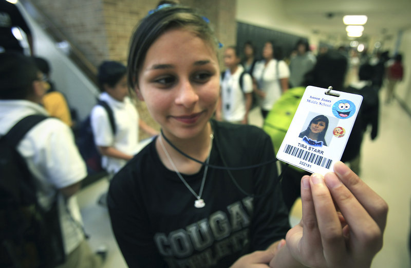 Tira Starr, an 8th grader at Anson Jones Middle School, shows her ID badge as students change classes in San Antonio, Texas.