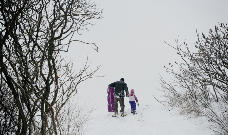 Ryan Guite of South Portland walks up the hill on the Eastern Prom in Portland with his daughter Emma, 4, after a trip down the hill on a sled Monday.