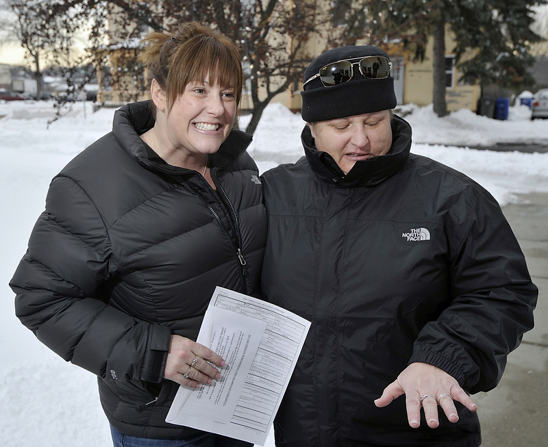 Heidi Caton holds the marriage license and her partner, Julie Nowell, looks at her rings as same-sex couples received marriage certificates at South Portland City Hall on Saturday. The wedding ceremony was planned for Saturday afternoon.