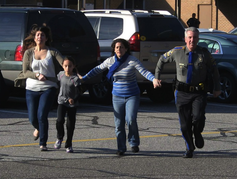 In this photo provided by the Newtown Bee, a police officer leads two women and a child from Sandy Hook Elementary School in Newtown, Conn., where a gunman opened fire, killing 26 people, including 20 children, Friday, Dec. 14, 2012. (AP Photo/Newtown Bee, Shannon Hicks)