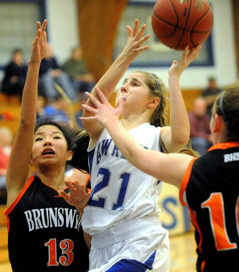 Lawrence High School's Dominique Lewis, center, drives to the hoop and draws the foul as Brunswick High School Gillian Doehring, left, and Emily Black, 10, right try to defend her in the first quarter Tuesday at Lawrence High School in Fairfield.