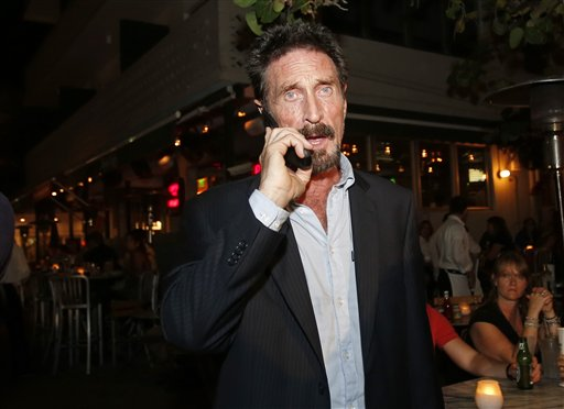 Anti-virus software founder John McAfee talks on his mobile phone as he walks on Ocean Drive in the South Beach area of Miami Beach, Fla., on his way to dinner Wednesday.