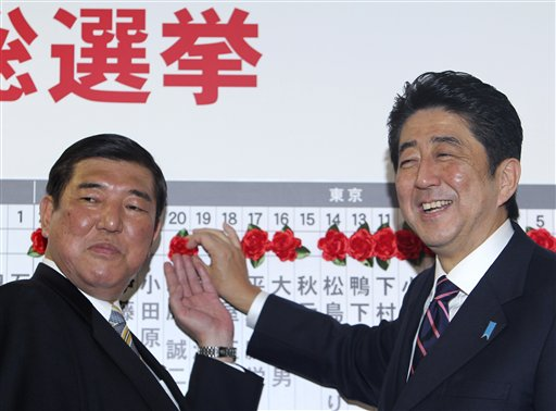 Japan's main opposition leader Shinzo Abe, right, of the Liberal Democratic Party, and the party secretary-general, Shigeru Ishiba, place a rosette on the name of one of those elected in parliamentary elections at the party headquarters in Tokyo on Sunday. The conservative LDP stormed back to power Sunday after three years in opposition, exit polls showed.
