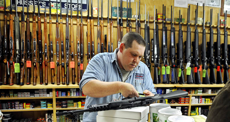 Jasen Pelletier prepares a Ruger Mini-14 rifle he sold in the gun department at Hussey's General Store on Saturday, in Windsor. Gun sales are strong, according to store staff.