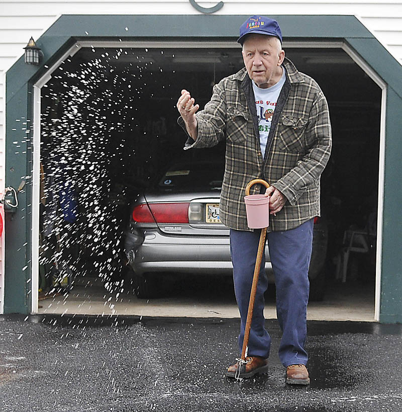 Hiram Cochran spreads salt Monday on the driveway of his Augusta home. Slick conditions greeted drivers across the state after rain and snow fell overnight, with icy mist persisting throughout the day. Cochran said he likes to keep the entrance to his home free of ice to accommodate getting the mail.