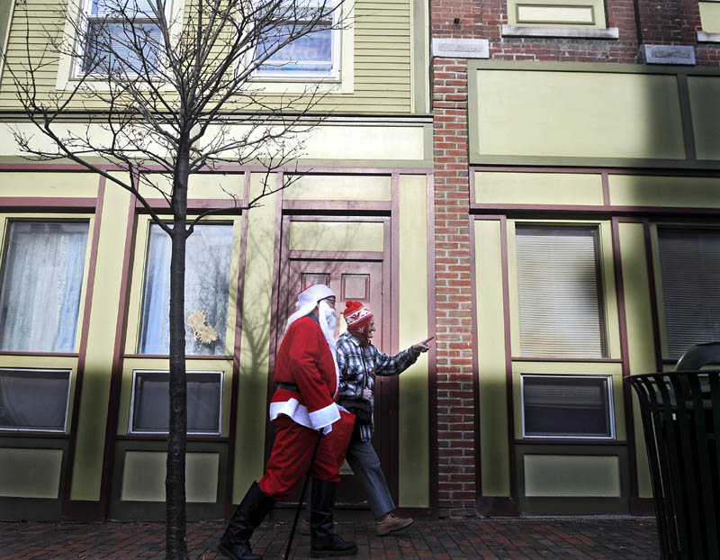 Santa Claus and Elizabeth Conary stroll down Water Street in Gardiner on Thursday. Stores were doing brisk business at midday in the middle of the holiday shopping season, beneath clear-blue skies. Kringle and Conary stopped and chatted with several shoppers and merchants during their constitutional through town.