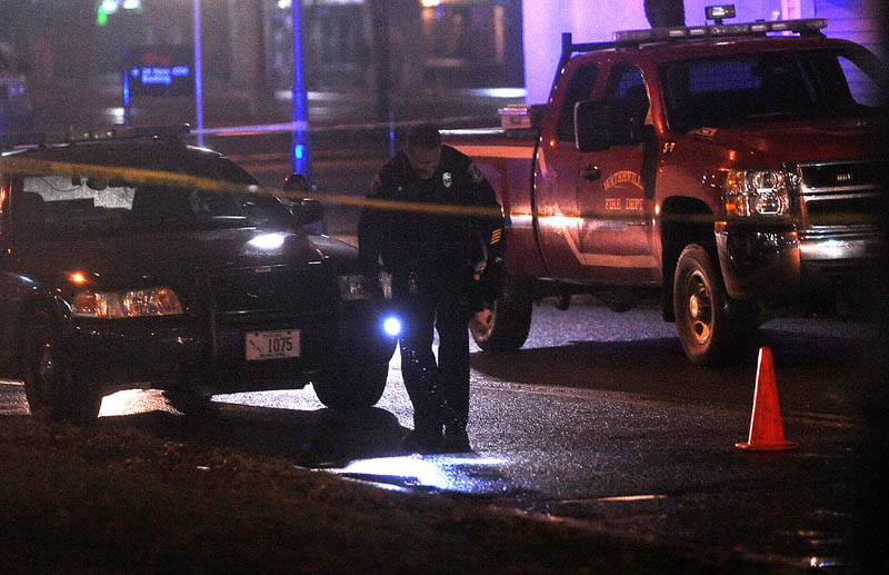 Staff photo by Michael G. Seamans Police investigate the scene where a man was shot on The Concourse late Tuesday night in Waterville.