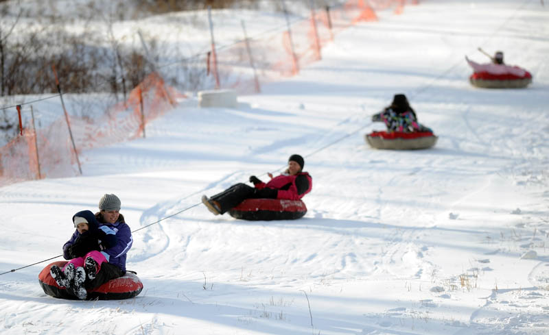 Tubing enthusiasts ride the rope tow to the top of the slope at Eaton Mountain Ski Area in Skowhegan on Friday. Snow tubing opened Friday for the season.
