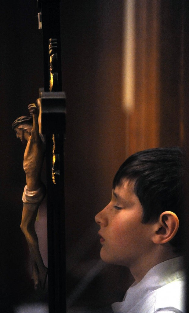 Edmund Couture,11, an altar server, struggles to keep his eyes open before the start of Midnight Mass at Sacred Heart Catholic Church on Pleasant Street in Waterville on Tuesday.