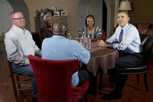 President Barack Obama visits with high school teacher Tiffany Santana, to his left, Velma Massenburg, Tiffany's mother, Jimmy Massenburg, Tiffany's father, in the blue shirt, and Richard Santana, far left, who works at a local Toyota dealership on Thursday in Falls Church, Va.